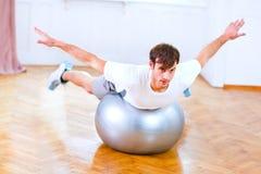 Homem saudável que faz exercícios na esfera da aptidão Foto de Stock Royalty Free