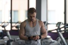 Homem saudável que usa Smartphone ao descansar foto de stock royalty free