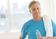 Homem seguro com toalha e garrafa de água no clube Imagem de Stock Royalty Free