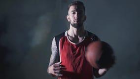 Homem seguro considerável do retrato no uniforme vermelho que guarda uma bola à disposição que olha na câmera no fundo escuro den video estoque