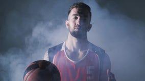 Homem seguro considerável no uniforme vermelho que guarda uma bola à disposição que olha na câmera no fundo escuro em uma nuvem filme
