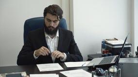 Homem seguro do homem de negócios que olha através dos papéis e que assina o documento na mesa no escritório moderno Horários com filme
