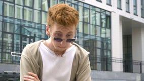Homem seguro do ruivo nos óculos de sol que estão na frente da construção video estoque