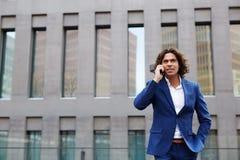 Homem seguro forte em uma estrada à moda do terno que fala no telefone fotos de stock royalty free