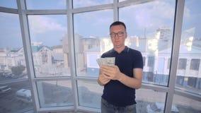 Homem seguro, sorrindo que conta e que mostra o dinheiro, dólares americanos na câmera filme