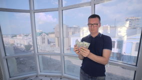 Homem seguro, sorrindo que conta e que mostra o dinheiro, dólares americanos na câmera video estoque
