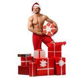 Homem 'sexy' de Santa Claus com uma pilha dos presentes Fotografia de Stock Royalty Free