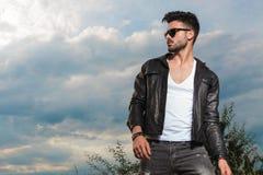 Homem 'sexy' novo no casaco de cabedal e nos óculos de sol que estão exteriores fotos de stock royalty free