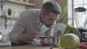 Homem smilling da habilidade considerável na camisa que cozinha a sopa na cozinha Conceito do alimento saudável, cozinhando em ca filme