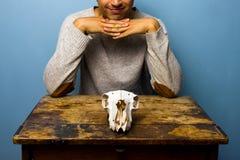 Homem Smirking com o crânio na mesa Foto de Stock