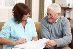 Homem sênior na discussão com o visitante da saúde em Ho Fotografia de Stock Royalty Free