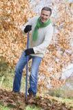 Homem sênior que arruma as folhas de outono Fotografia de Stock Royalty Free