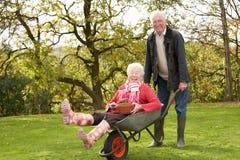Homem sênior que dá o passeio da mulher no Wheelbarrow Imagens de Stock Royalty Free