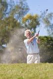 Homem sênior que joga o tiro de golfe em um depósito Foto de Stock
