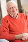 Homem sênior que relaxa na cadeira em casa Imagem de Stock Royalty Free