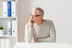Homem sênior que senta-se na tabela Foto de Stock Royalty Free
