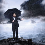 Homem sob o guarda-chuva que verific para ver se há a chuva Imagem de Stock