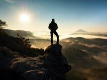 Homem sobre a montanha O caminhante escalou no pico da rocha acima do vale nevoento fotografia de stock royalty free