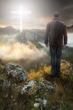 Homem sobre a montanha que olha Christian Cross Fotos de Stock
