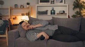 Homem sonolento da pessoa que olha a tevê comer a pipoca que encontra-se no sofá em casa apenas video estoque