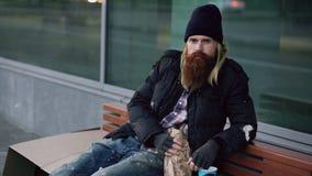 Homem sonolento desabrigado bêbado que sorri e que olha a câmera ao sentar-se no banco no passeio foto de stock