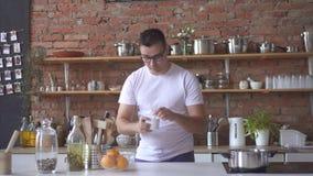 Homem sonolento no café bebendo da manhã na cozinha video estoque