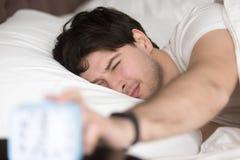 Homem sonolento que desliga o despertador, hora de acordar imagem de stock