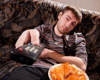 Homem sonolento que presta atenção à tevê Fotografia de Stock