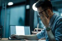 Homem sonolento que trabalha tarde no escritório fotos de stock
