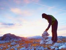 Homem sozinho do caminhante na parte superior do pyrmid alpino da construção da montanha dos seixos imagem de stock royalty free