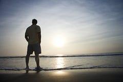 Homem sozinho na praia. Imagens de Stock
