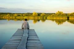 Homem sozinho que senta-se na borda de um cais imagens de stock