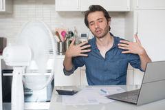 Homem suado que tenta refrescar do calor com fã Fotos de Stock Royalty Free