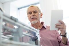 Homem superior agradável que estabelece a impressora 3D com tabuleta Imagem de Stock Royalty Free