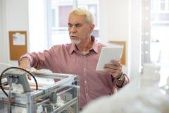 Homem superior agradável que muda configurações da impressora 3D imagem de stock