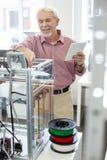 Homem superior alegre que aprende como usar a impressora 3D Imagem de Stock