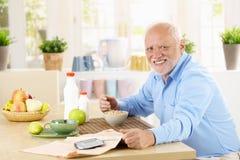 Homem superior alegre que come o café da manhã foto de stock