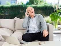 Homem superior alegre que responde a Smartphone no patamar Fotografia de Stock Royalty Free
