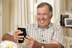 Homem superior aposentado feliz que senta-se na fotografia de Sofa At Home Looking At Fotos de Stock