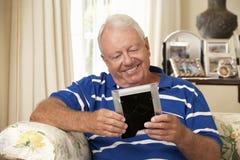 Homem superior aposentado feliz que senta-se na fotografia de Sofa At Home Looking At Fotografia de Stock