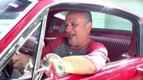 Homem superior aposentado que liga o motor do carro clássico restaurado video estoque