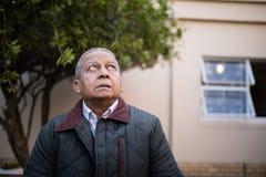 Homem superior aposentado que olha acima fotos de stock royalty free