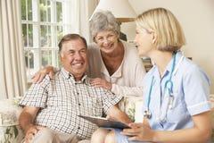 Homem superior aposentado que tem o exame médico completo com enfermeira At Home imagens de stock