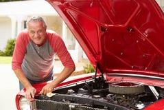 Homem superior aposentado que trabalha no carro clássico restaurado imagem de stock royalty free
