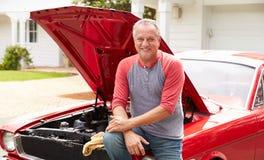 Homem superior aposentado que trabalha no carro clássico restaurado imagem de stock