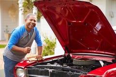 Homem superior aposentado que trabalha no carro restaurado foto de stock royalty free