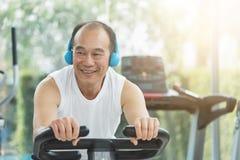 Homem superior asiático na bicicleta de exercício o gym foto de stock royalty free