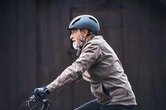 Homem superior ativo com fundo escuro de ciclagem dos againts do ar livre do capacete da bicicleta foto de stock