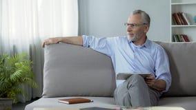 Homem superior bem sucedido que senta-se no sofá com tabuleta, usando o dispositivo moderno para o trabalho fotografia de stock
