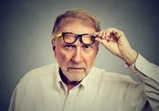 Homem superior cético com os vidros que olham o fotos de stock royalty free